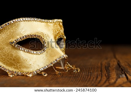 Golden decorated Venice mask on rustic wooden table - stock photo