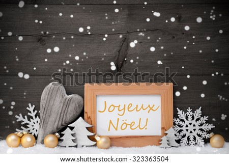 Golden Decoration On Snow. Heart, Christmas Tree Balls, Snowflakes, Christmas Tree,Picture Frame.French Joyeux Noel Mean Merry Christmas. Rustic, Vintage Gray Wooden Background. Black And Withe - stock photo