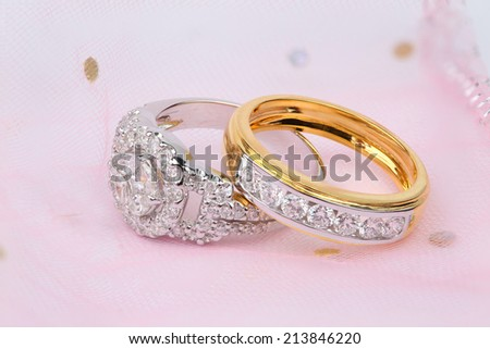 Golden diamond ring and contemporary diamond ring on pink background - stock photo