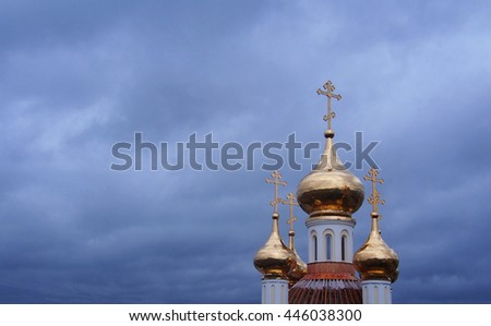 Golden domes of orthodox church and cloudy sky