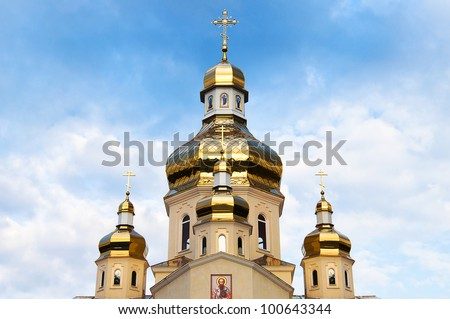 Golden domes of Orthodox Church on the cloudy blue sky - stock photo