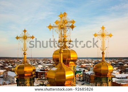 Golden domes of the Orthodox church in Russia on the blue sky and town background partially covered with snow. - stock photo
