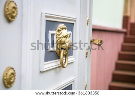 Golden door handle lion's head, open the white wooden door, red stone steps, Speyer, Germany  - stock photo