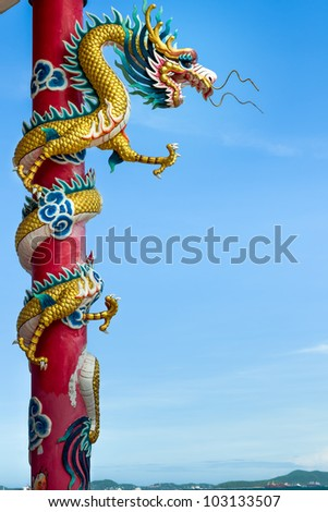 Golden dragon wrapped around red pole, Chinese-style building