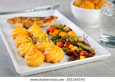 Golden duchess potatoes with grilled chicken and mexican vegetables