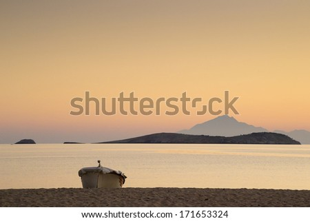 Golden dusk light at a beach near Potos on the island of Thassos, Greece with mount Athos in the distance. - stock photo