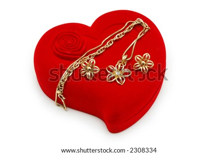 Golden earrings and chain on red heart-shaped box - stock photo