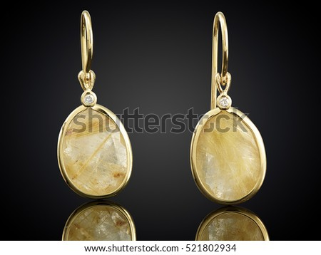 Golden earrings with gemstone isolated on black background.