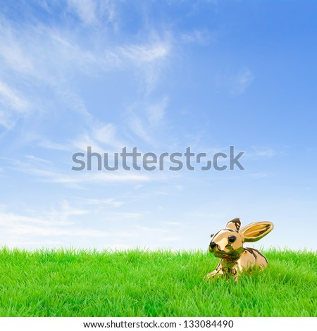 Golden easter bunny, sitting in bright field at a fine spring day. - stock photo