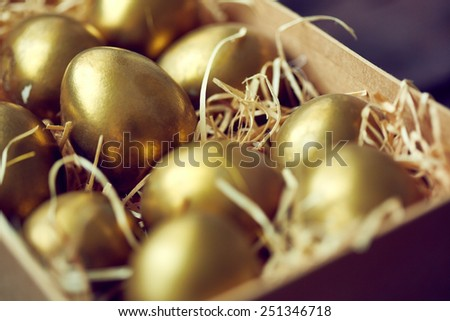 Golden Easter eggs in box or container - stock photo