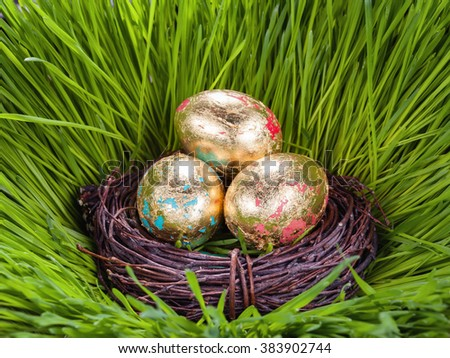 Golden Easter eggs in the nest on green grass of spring - stock photo