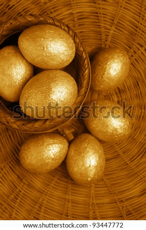 Golden Easter eggs with craquelures in wicker basket. - stock photo