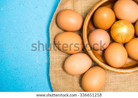 Golden egg and egg in a cup on a wooden background.  - stock photo