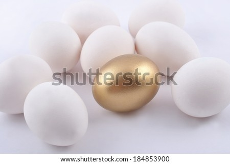 Golden egg and jast eggs on a white background - stock photo
