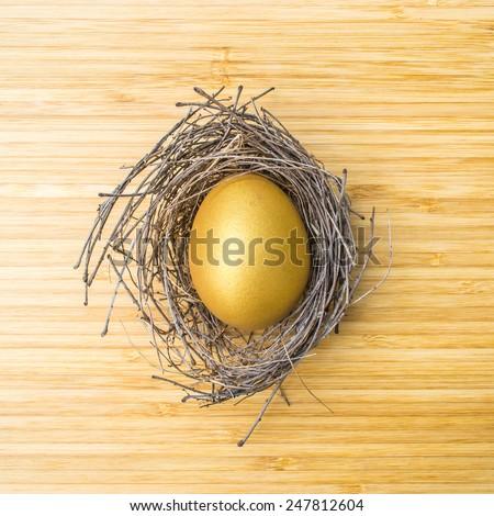 Golden egg in a nest on wooden background: A golden egg opportunity - stock photo