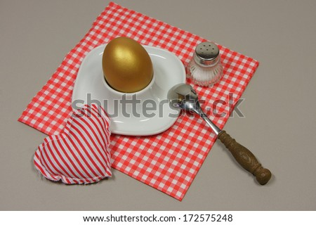 golden egg in an egg cup on a red patterned napkin with spoon and salt shaker - stock photo