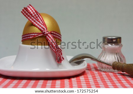 golden egg in an egg cup on a red patterned napkin with spoon and salt shaker loop - stock photo