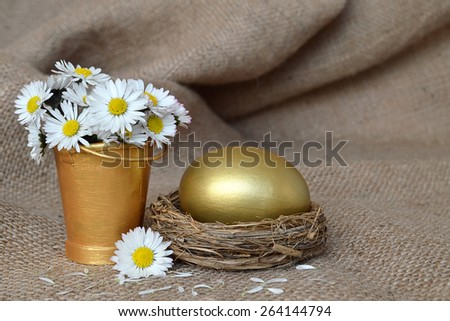 Golden egg in nest and daisies on canvas - stock photo