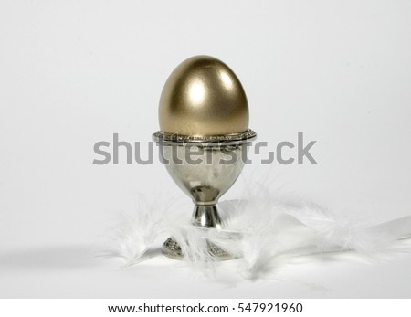 golden egg in silver cup