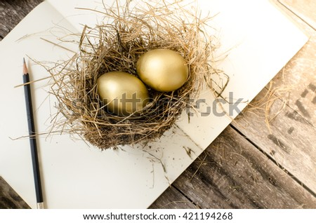 golden egg in the nest, notebook,glasses, pencil over wooden background