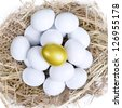 Golden egg inside a nest together with common white eggs, isolated on white - stock photo