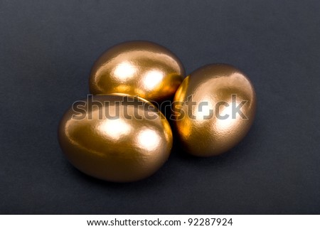 Golden eggs. A symbol of making money and successful investment on black background - stock photo