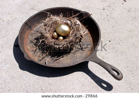 golden eggs in a bird nest in a frying pan representing finincial freedom and security in the image of a Nest Egg - stock photo
