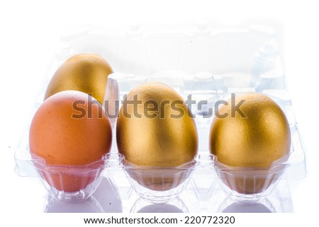 Golden eggs in plastic pack isolated in white. - stock photo