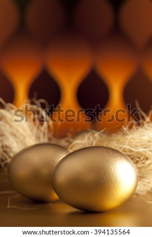 Golden eggs on abstract patterned background - stock photo