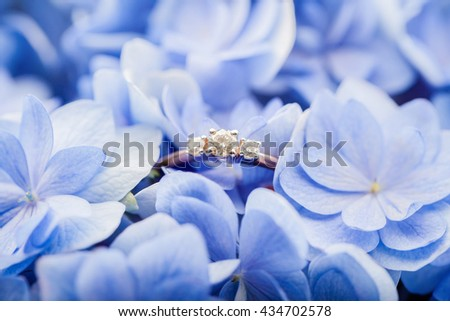 Golden engagement ring with diamonds in blue flowers on background - stock photo