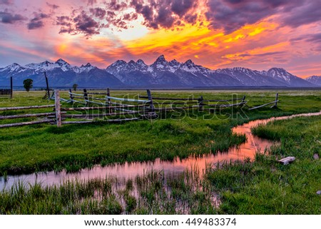 Golden Fiery Sunset at Grand Teton - A colorful spring sunset at Teton Range, seen from an abandoned old ranch in Mormon Row historic district, in Grand Teton National Park, Wyoming, USA.  - stock photo