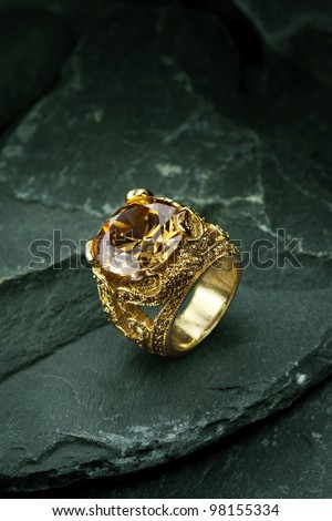 Golden finger ring with yellow precious stone - stock photo