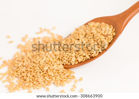 Golden flax seeds close up on a wooden spoon isolate on white