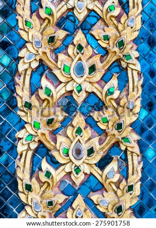 Golden flower stucco in traditional Thai style on the temple wall. - stock photo