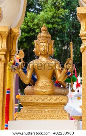 golden four face Buddha statue on pedestal - stock photo