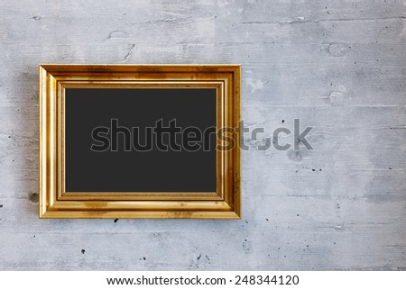 Golden frame with blank copy space hanging on the concrete wall - stock photo