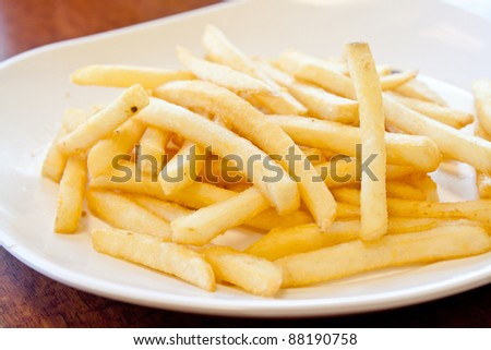 Golden French fries in white plate