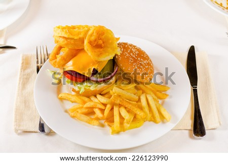 Golden French fries with a cheeseburger topped with crispy onion rings on a beef patty served for lunch - stock photo