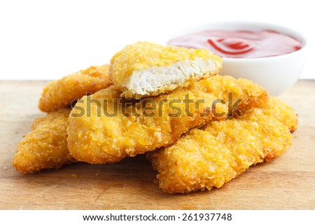 Golden fried chicken strips on wood board. Pot of ketchup. - stock photo