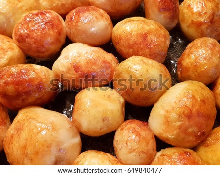 Golden fried young potatoes on the sasly are whole round.