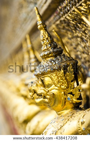 Golden Garudas statues in a row on outside walls of Temple of the Emerald Buddha, Grand Palace, Bangkok, Thailand. Focus on the first statue with blurred background