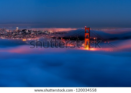 Golden Gate at night surrounded by fog - stock photo