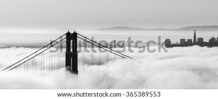 Golden Gate Bridge and skyscrapers are  shown in a fog , San Francisco, California