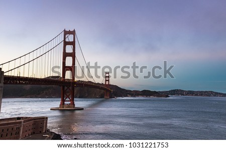 Golden Gate bridge at dawn with pink sky and calm water , San Francisco , California