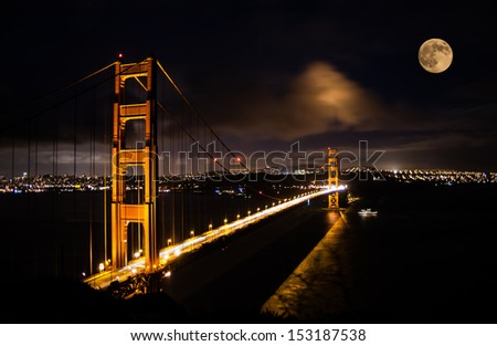 Golden Gate bridge at night with full moon shining on San Francisco skyline - stock photo