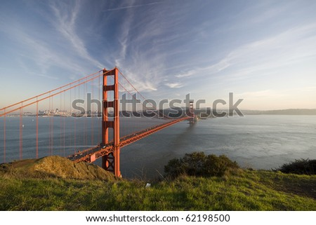 Golden Gate Bridge at sunset with beautiful grass as foreground