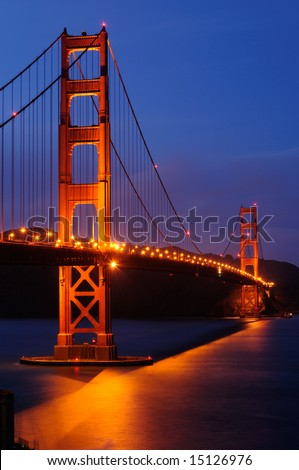Golden Gate Bridge illuminated at dusk. Shot from a hill over Fort Point, San Francisco, California.