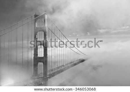 Golden Gate Bridge in black and white with the fog rolling in and the second tower visible in the distance.  Artistic in composition and lighting.