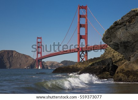 Golden Gate Bridge in California and spray of the sea on the shore
