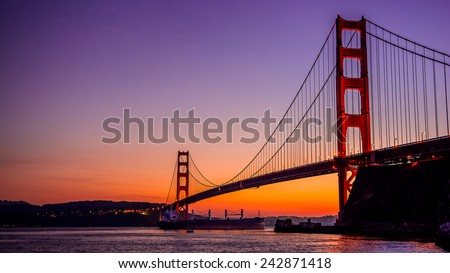 Golden Gate Bridge in San Francisco, CA, as seen from Vista Point near Horseshoe Bay-California-Central-Coast with super tanker passing underneath the bridge. - stock photo